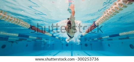 Professional man swimmer inside swimming pool. Underwater panoramic image. - stock photo