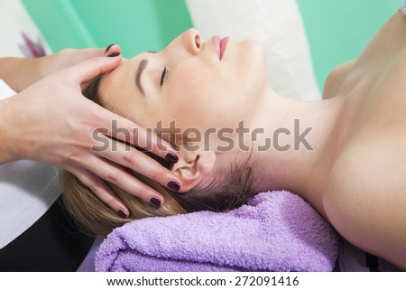 Professional massage therapist massaging a young woman face - stock photo
