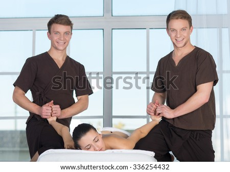 Professional massage treatment. Two twin brothers professional physiotherapist masters of massage are doing massage to their patient in a spa. Massage spa healthy concept. Double couple massage