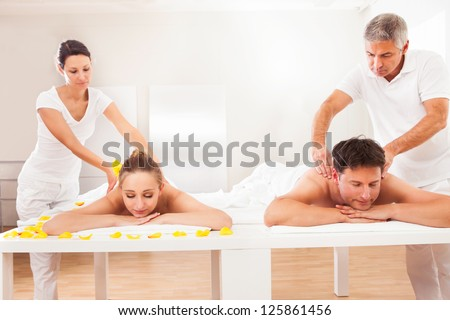 Professional masseurs in a spa giving back massages to an attractive husband and wife lying side by side - stock photo