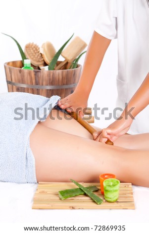 professional masseuse making a bamboo massage in the back in spa - stock photo