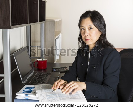 Professional Mature Asian woman working on Personal Income Taxes with tax table booklet, computer, coffee cup with spoon on desk