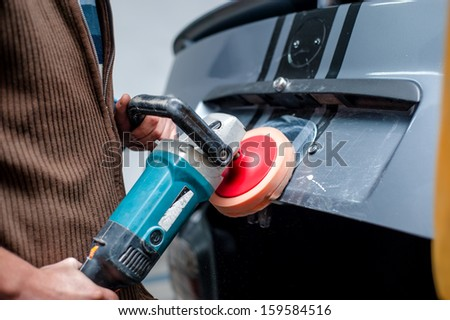 professional mechanic cleaning the metal surface of the bodywork of a car with power buffer machine. Polish procedure and car care concept - stock photo