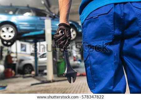 Professional Mechanic Repairing Car Engine in Garage.
