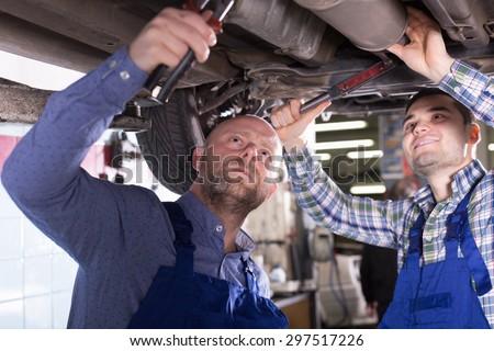 Professional mechanics repairing car of client - stock photo