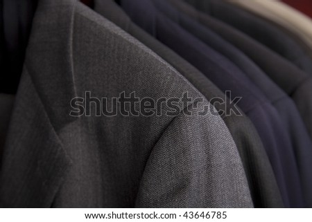 Professional men's suits hanging on a rack. - stock photo