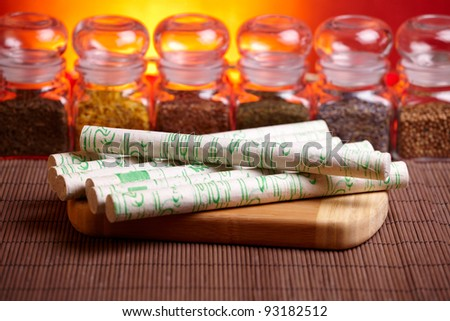 Professional moxa sticks on wooden desk with TCM herbs in glass jars in background - stock photo