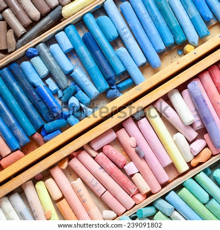 Professional multicolored pastel crayons in wooden artist box closeup, top view. - stock photo
