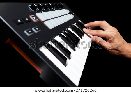 professional musician hand playing on studio keyboard synthesizer, focus to finger & isolated on black for dance , groove, remix, dubstep music background concept - stock photo