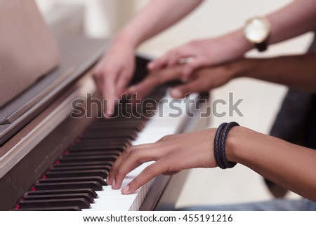Professional musician playing outdoors. Closeup of keyboard of piano. Man playing piano while lady explaining him something. - stock photo