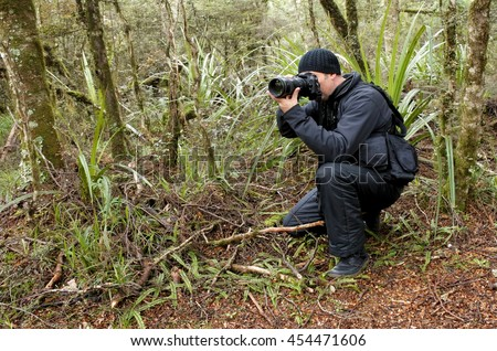 Professional nature, wildlife and travel photographer shooting outdoors during on location photo assignment in Tongariro National Park rain forest, New Zealand. copy space. - stock photo