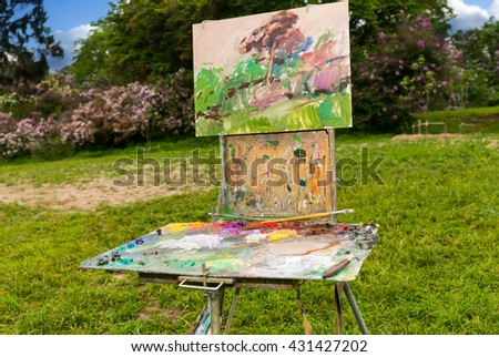 Professional old painter's sketchbook  with different artist's equipment colorful palette paletteknife paints and paintbrushes outdoors - stock photo