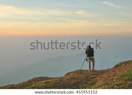 Professional on cliff. Nature photographer takes photos . Dreamy fogy landscape,  winter blue orange misty sunrise in a beautiful valley below.