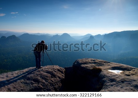 Professional on cliff. Nature photographer takes photos with mirror camera on peak of rock. Dreamy fogy landscape, spring orange pink misty sunrise in a beautiful valley below.  - stock photo