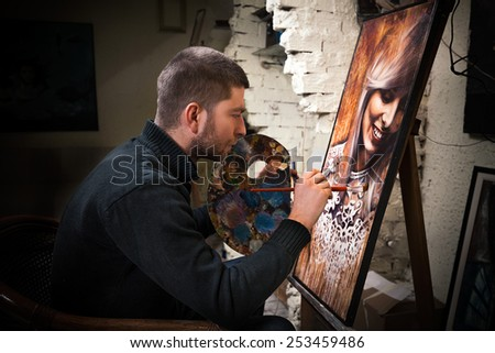 Professional painter at his art studio, working on a oil painting portrait. - stock photo