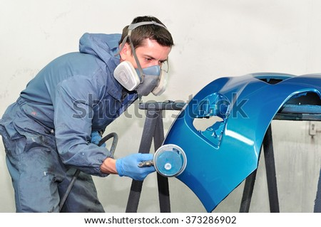 Professional painting of blue car bumper. - stock photo
