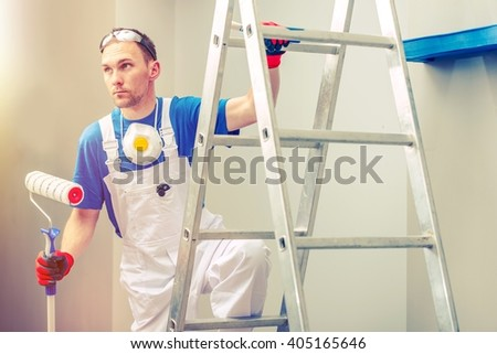 Professional Painting. Professional Painter with Painting Roller on the Ladder.