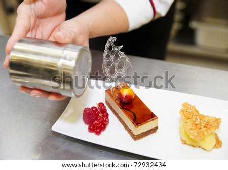 Professional pastry chef is decorating a dessert - stock photo