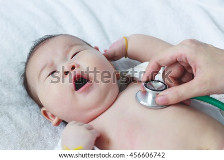 Professional pediatrician examining infant. Doctor using a stethoscope to listen to kid's chest checking heartbeat. Two months baby asian girl lying on sickbed in hospital. - stock photo