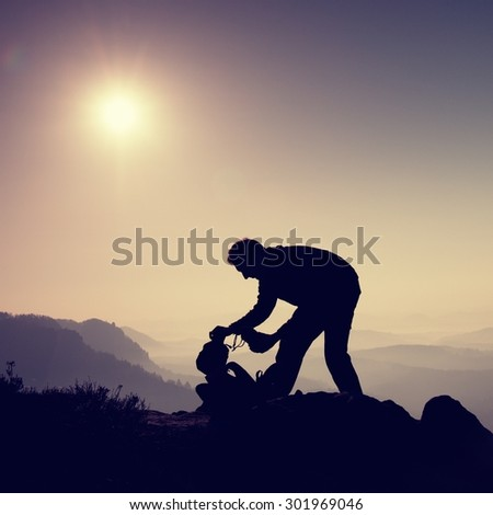 Professional photographer is packing camera into backpack on peak of rock. Dreamy fogy landscape, spring orange pink misty sunrise in a beautiful valley below - stock photo