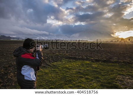 professional photographer takes a picture sunset in the mountains - stock photo