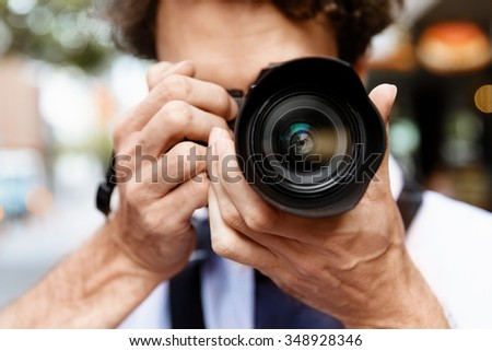 Professional photographer taking picture in city - stock photo