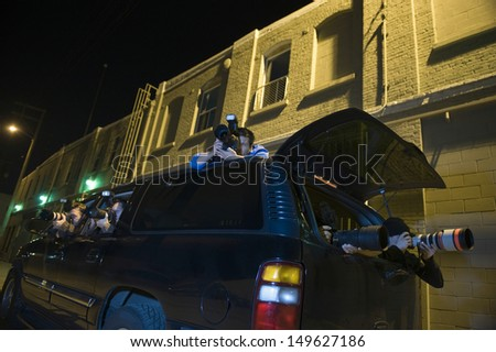 Professional photographers with telephoto lens in car - stock photo