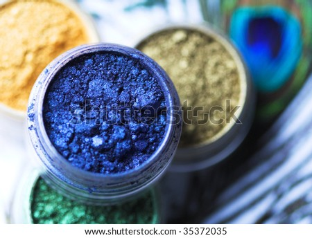 Professional powder eye-shadows of bright colors and peacock feather - stock photo