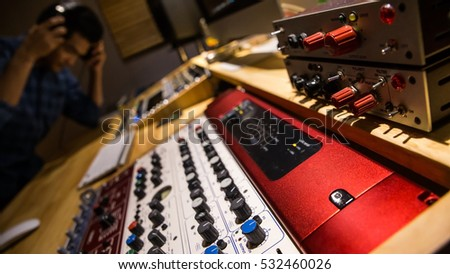 "Professional recording studio equipments in the 19"" rack table with an engineer in the background."