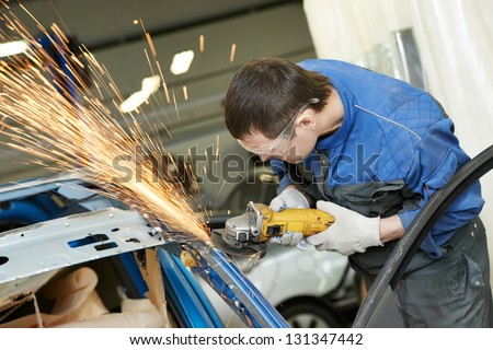 professional repairman worker in automotive industry grinding metal body car with sparks - stock photo
