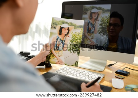 Professional retoucher working on photograph of young woman, view over the shoulder - stock photo