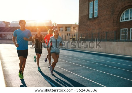 Professional runners running on a race track. Multiracial athletes practicing on race track in stadium on a bright sunny day. - stock photo
