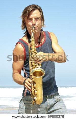 Professional saxophone player at the beach - stock photo