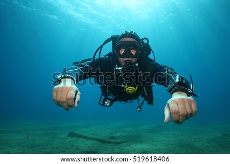 Professional scuba diver with black drysuit diving underwater in the ocean