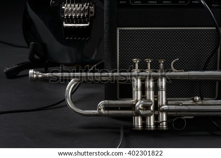 Professional silver trumpet in foreground. Some parts of guitar amp and electric guitar in black background.  - stock photo
