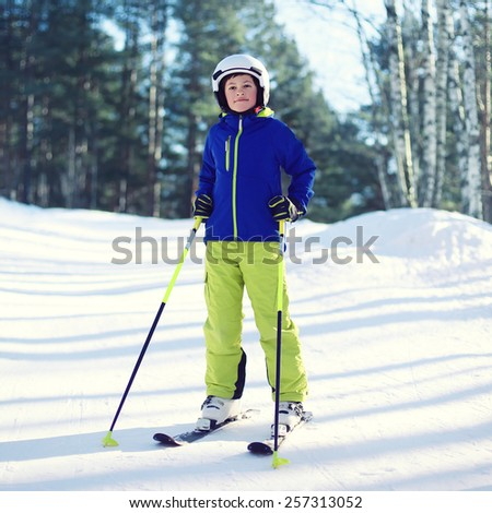 Professional skier boy in sportswear and helmet, sunny winter day - stock photo
