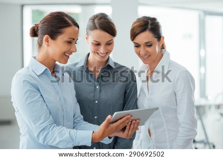 Professional smiling business women standing in the office and using a touch screen tablet, they are enjoying and watching the screen