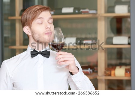 Professional sommelier. Close-up of a young sommelier testing wine flavor with his eyes closed - stock photo