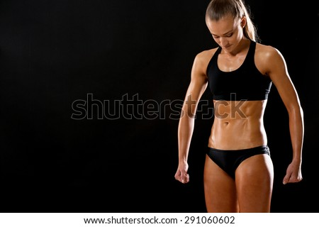 Professional sportswoman in studio. Fit and no fat young woman showing abs and thin skin. - stock photo