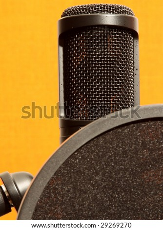 professional studio microphone with anti-pop on orange background