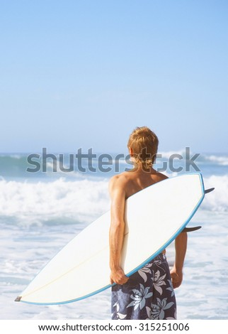 Professional Surfer holding a Surf  - stock photo