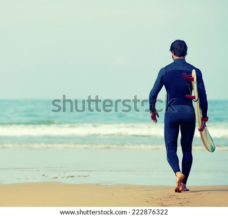 Professional surfer man dressed in wetsuit ready to surfing on big waves walking on the beach, young beautiful surfer carrying surfboard while walking on the beach, perfect sunny day, filtered image - stock photo