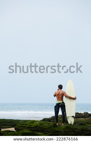 Professional surfer man in black wetsuit standing on the rocks covered with moss enjoying beautiful view of ocean, surfer holding his favorite surfboard looking for the ocean waiting big waves - stock photo