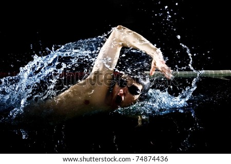 Professional swimmer crawl freestyle isolated black background - stock photo