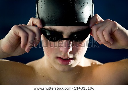 professional swimmer portrait isoalted blue background - stock photo