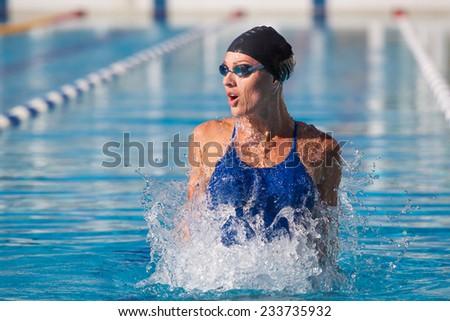 professional swimmer, water splashing, goggles and swimming cap - stock photo
