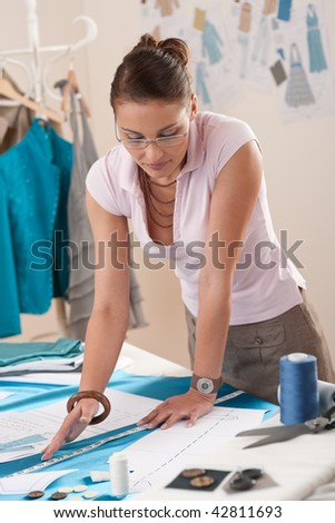 Professional tailor working with fashion sketches at studio - stock photo