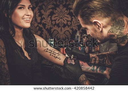 Professional tattoo artist makes a tattoo on a young girl's hand.  - stock photo