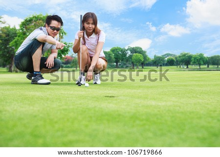 Professional teaching young woman golfer to play golf - stock photo
