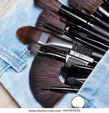 Professional tools of make-up artist in blue jeans pocket. Sponge tip applicators and makeup brushes: for applying foundation, powder, blush, eyeshadow, eyebrow brushes and others. Selective focus - stock photo